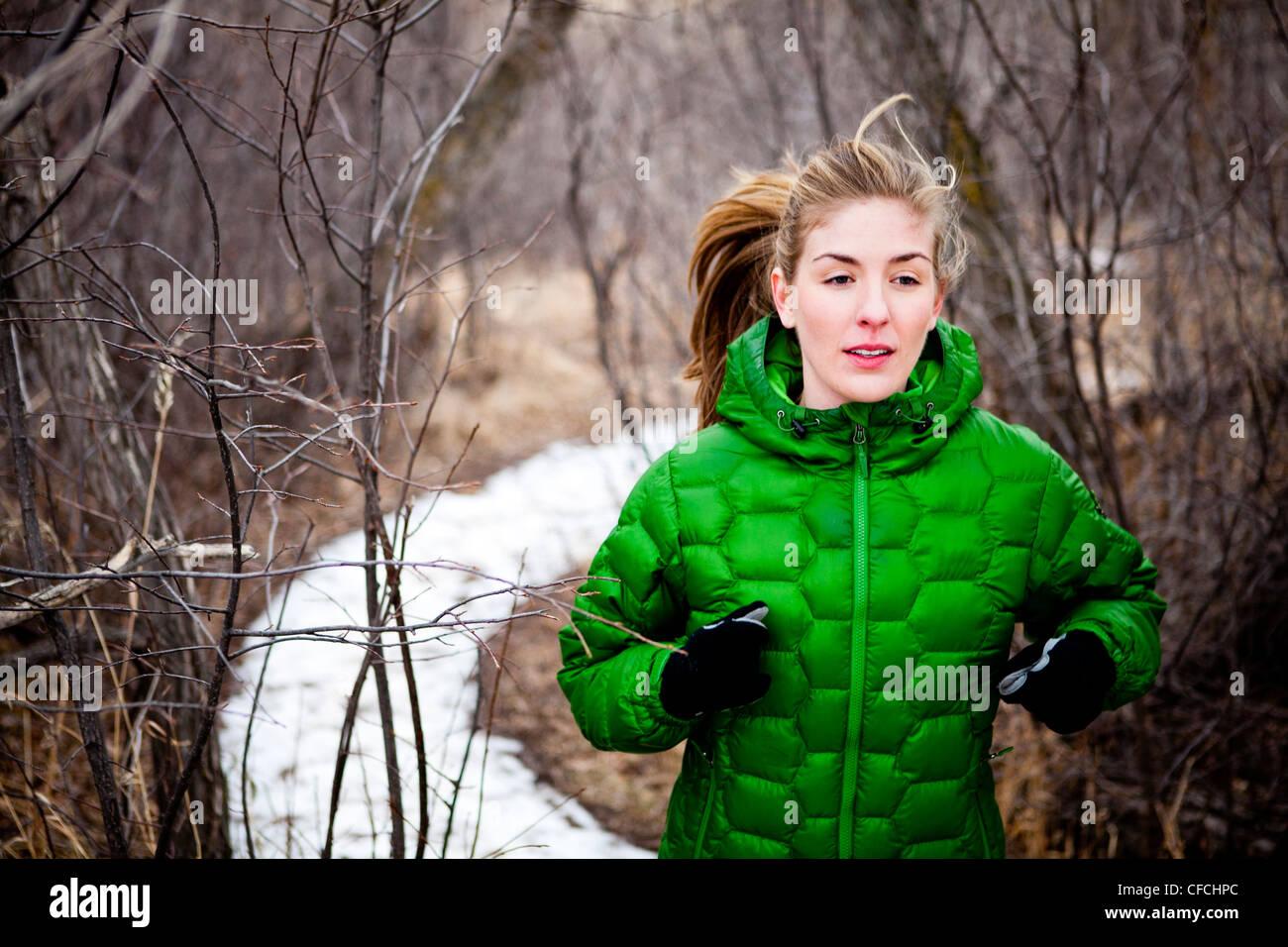 Una joven mujer corre a lo largo de un camino cubierto de nieve a través de deshojado árboles caducifolios, Imagen De Stock
