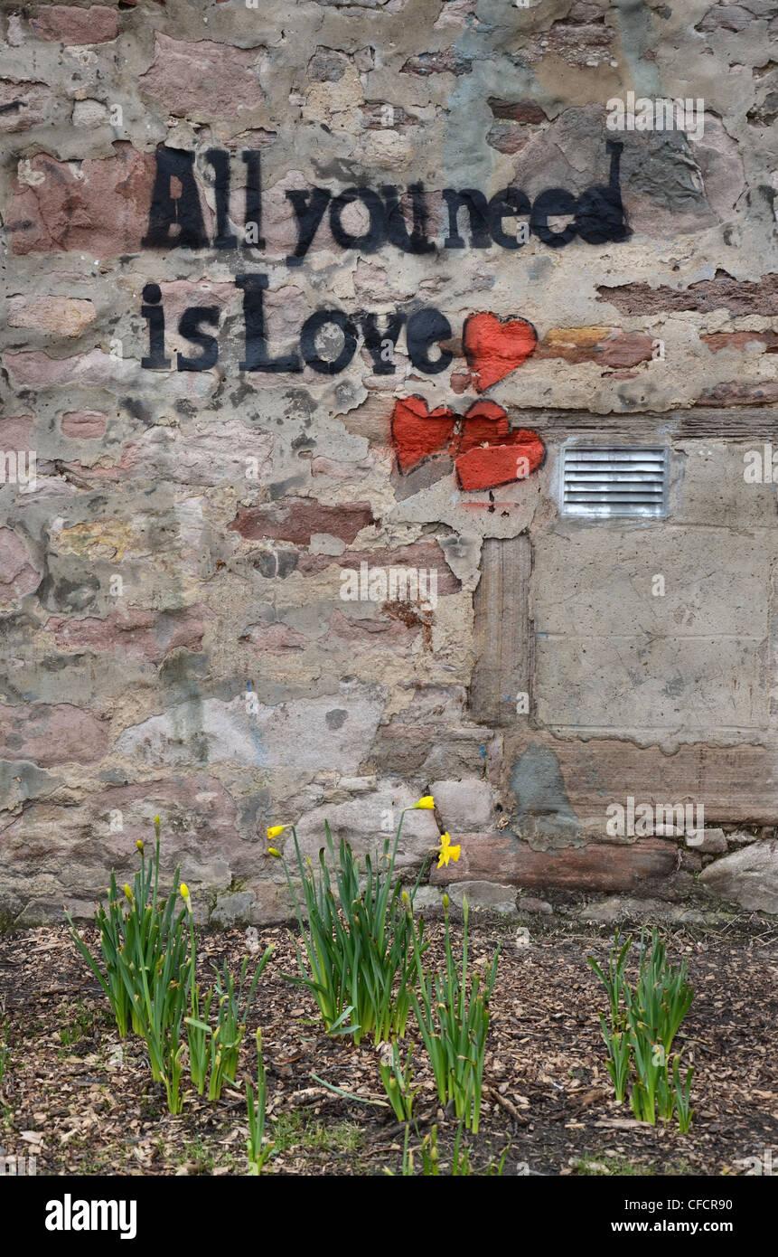 """""""Todo lo que necesitas es amor' graffiti en una pared de Edimburgo y el título de una canción de los Beatles. Foto de stock"""