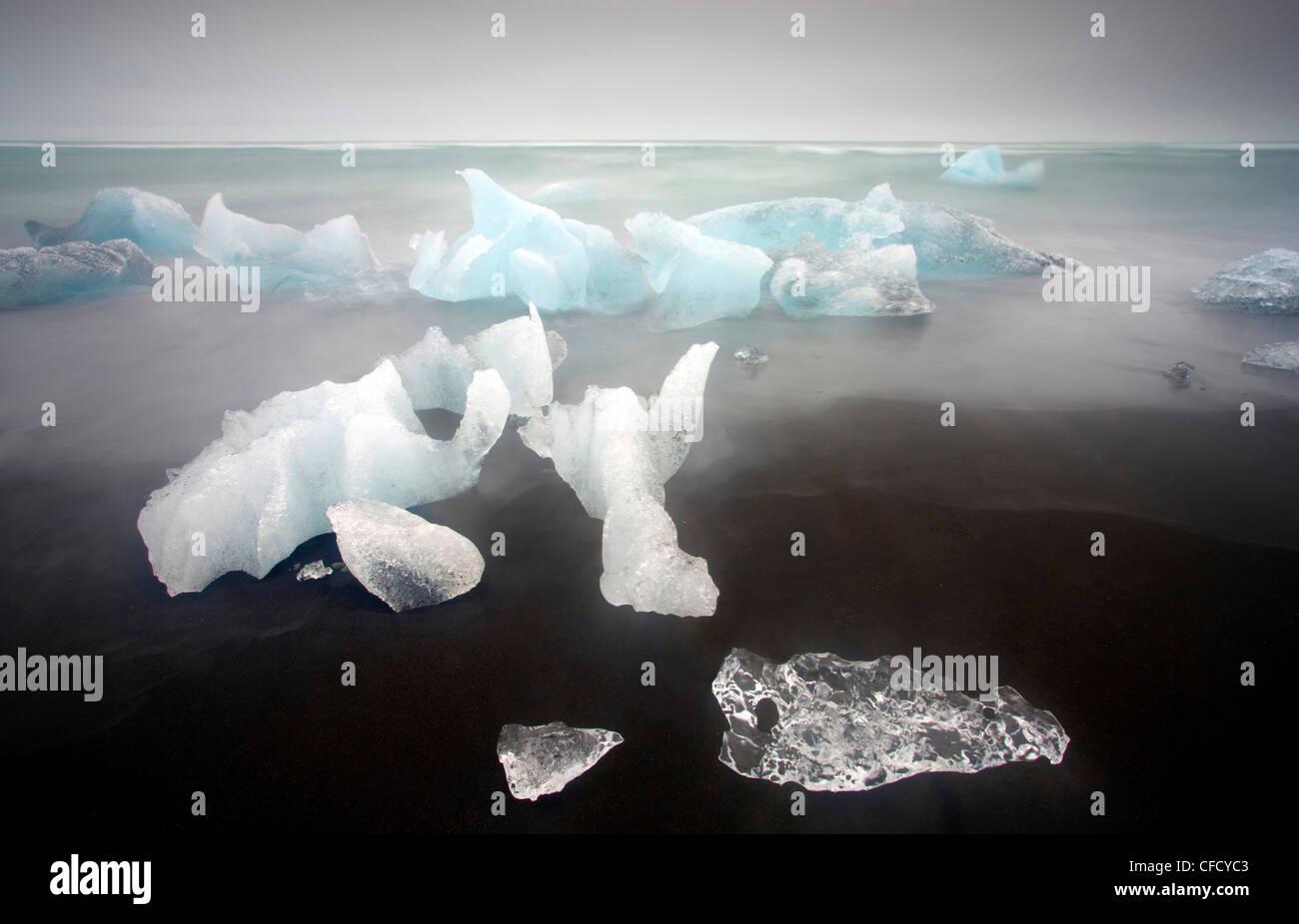 Los icebergs desde la Laguna glaciar Jokulsarlon arrastrados hasta una cercana playa de arena volcánica en el Océano Atlántico Norte, Islandia Foto de stock