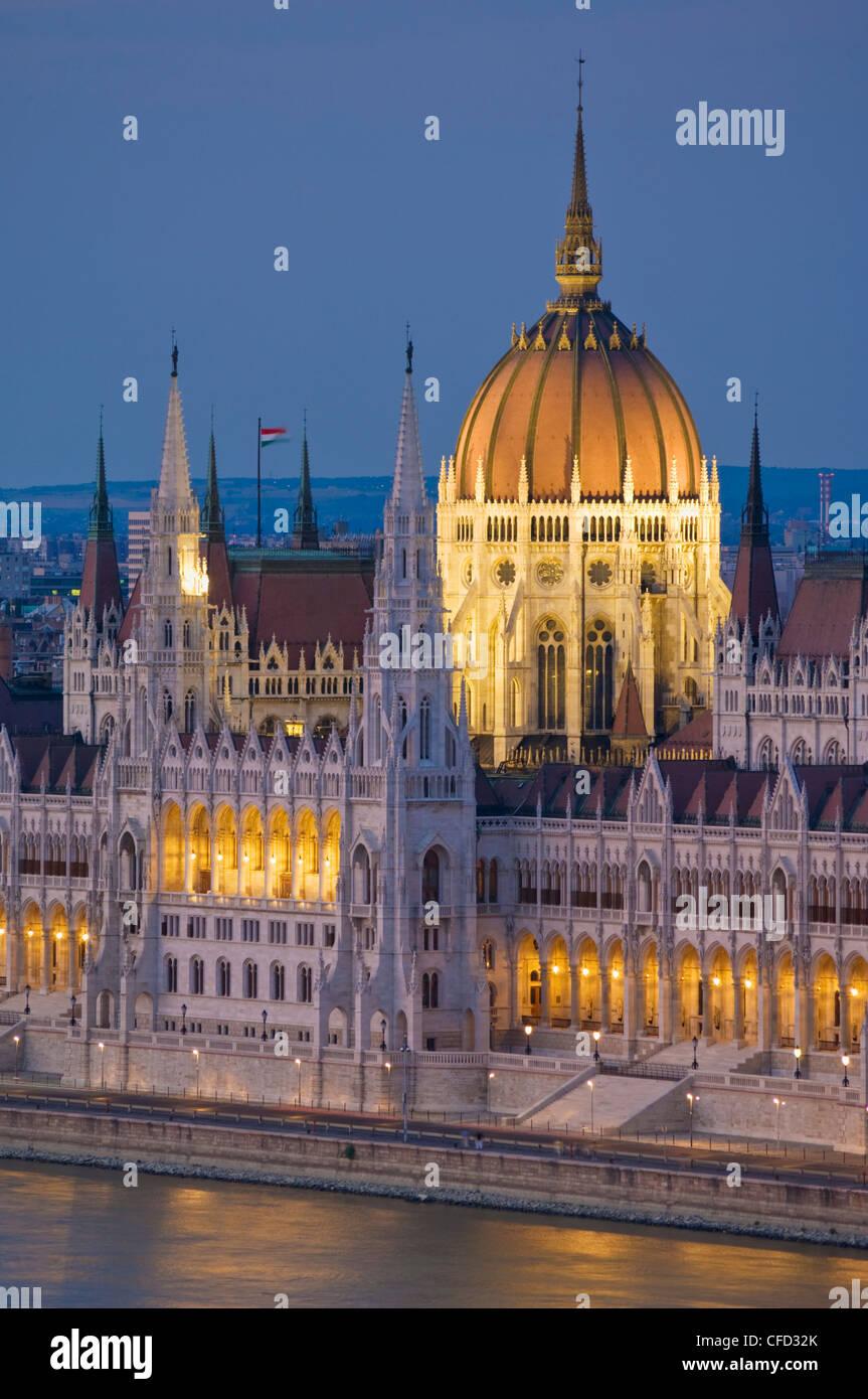 El Parlamento húngaro, iluminado en la noche, y el río Danubio, Budapest, Hungría Imagen De Stock