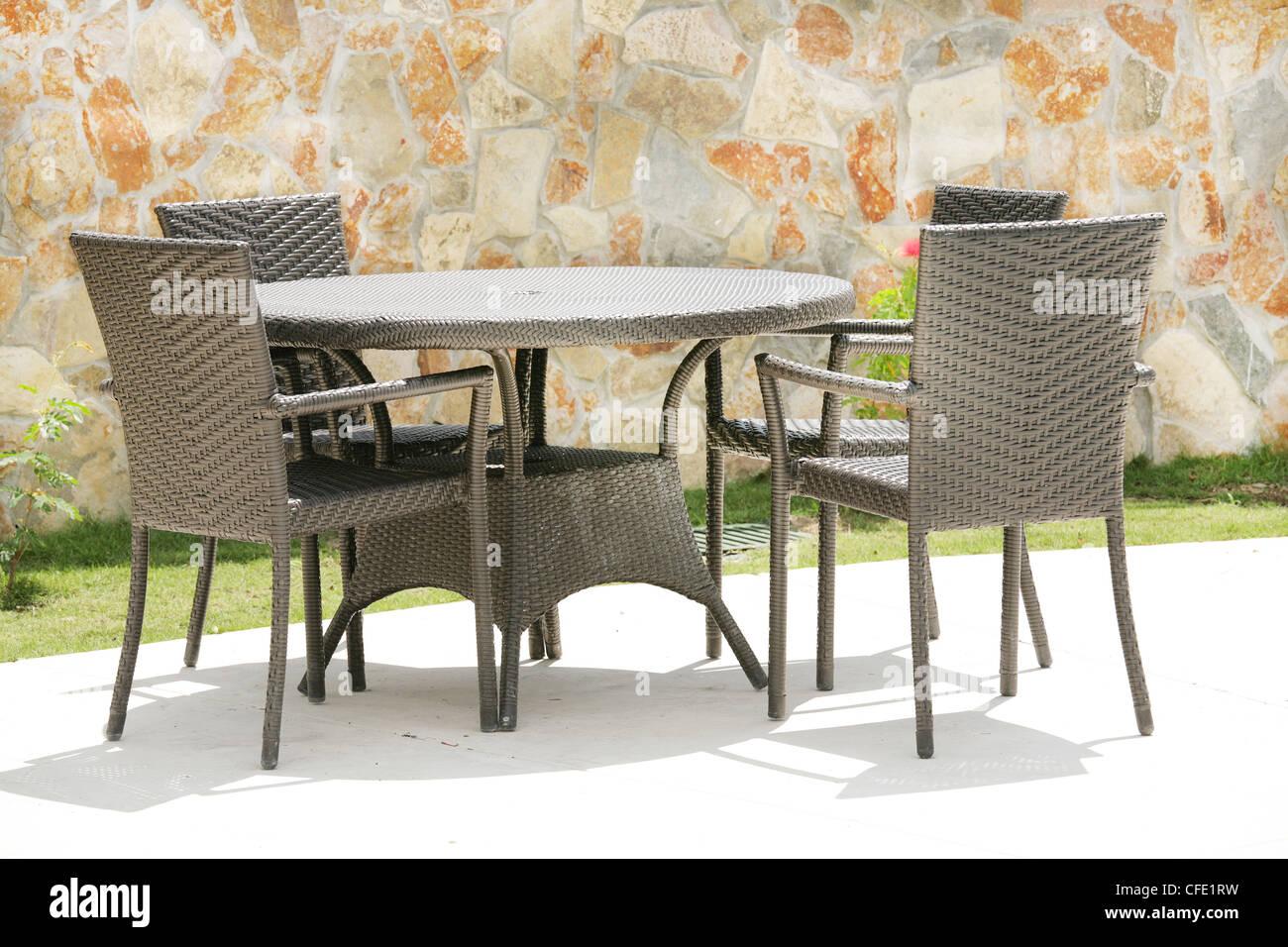 Mesa y sillas en un jardín tropical con una textura de pared de ...