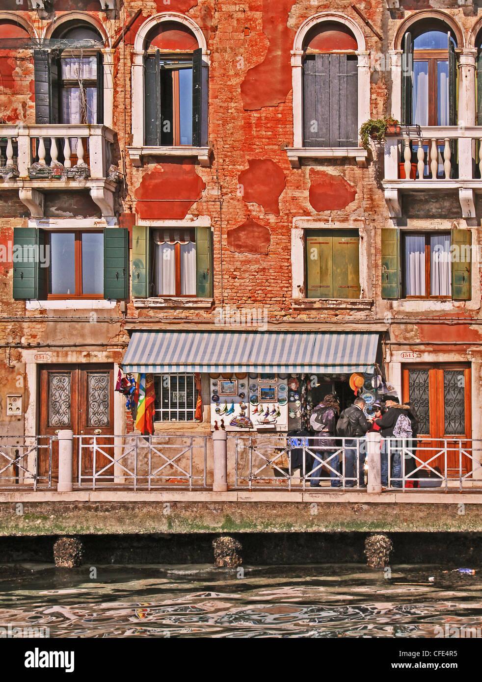 Venecia, antiguo edificio frente al agua y turistas en frente de una tienda de regalos Imagen De Stock