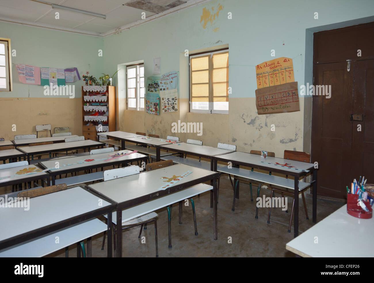 Filas de pupitres vacíos dentro del aula de escuela primaria escasamente amueblada en Sal Rei, Boa Vista, Islas Imagen De Stock