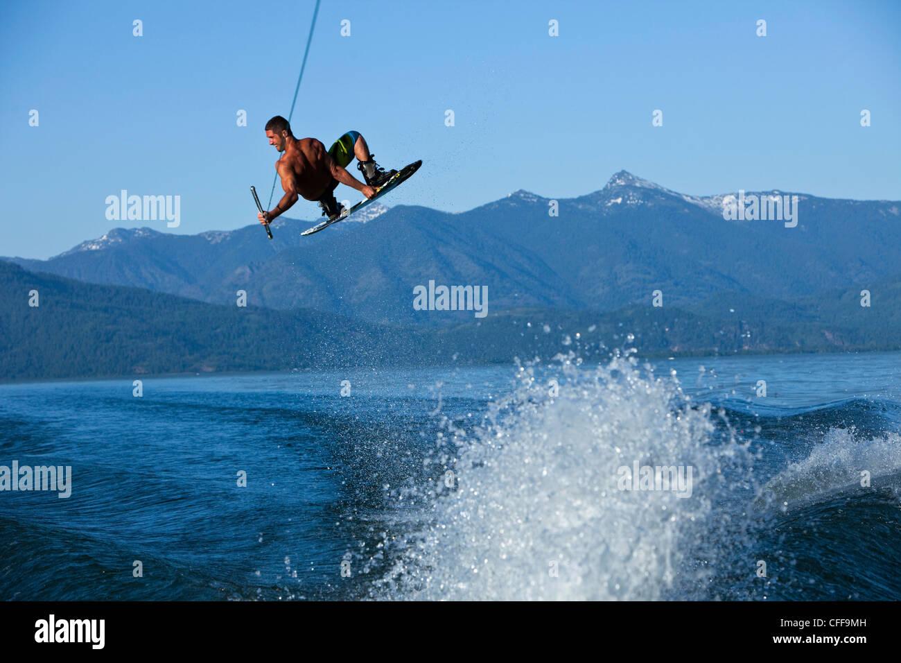 Un macho atlética wakeboarder impulsa a través de la estela al atardecer en un lago en Idaho. Imagen De Stock