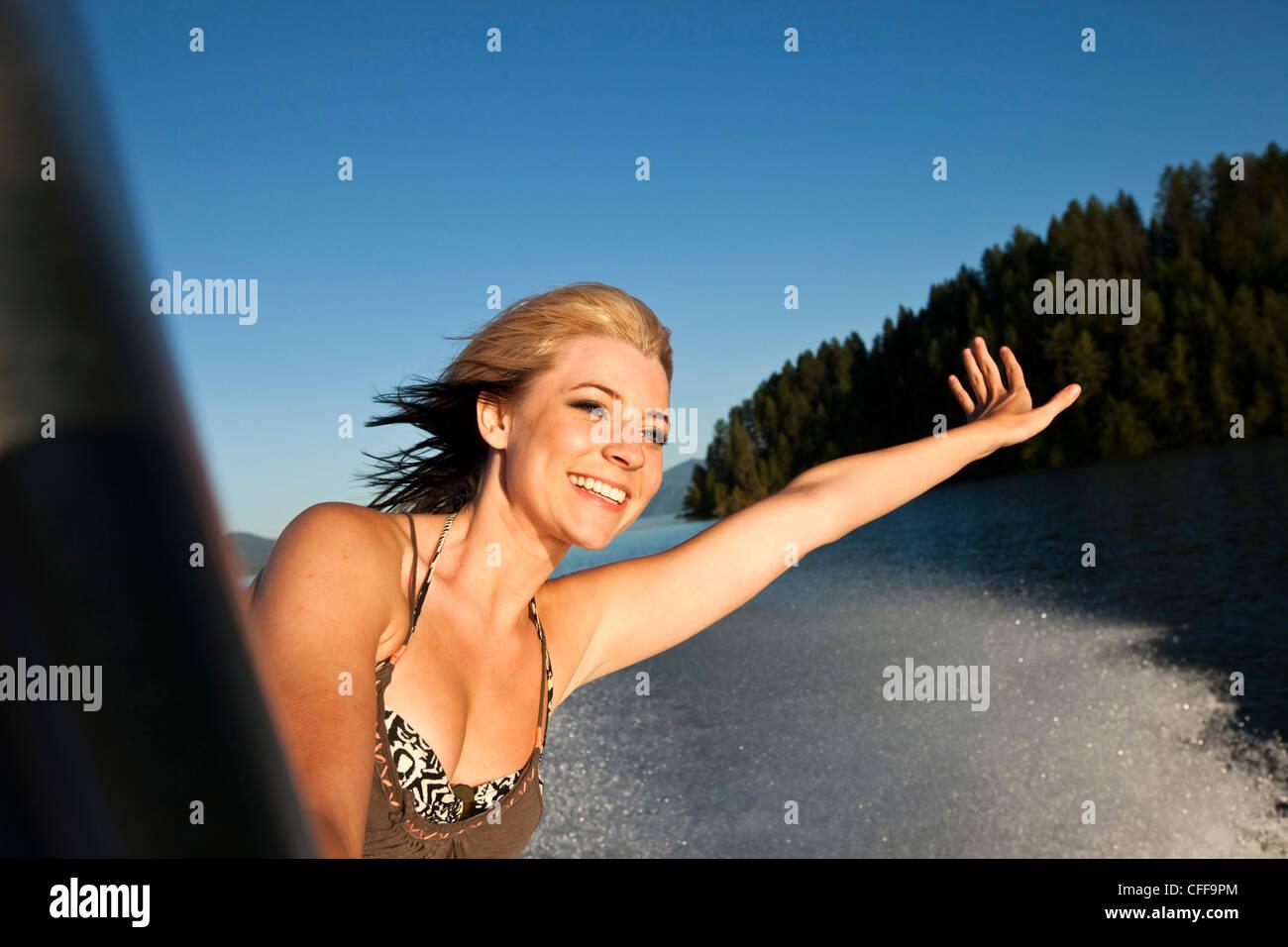 Una joven y bella mujer sonriendo y sosteniendo su mano al atardecer en un barco wakeboard en Idaho. Imagen De Stock