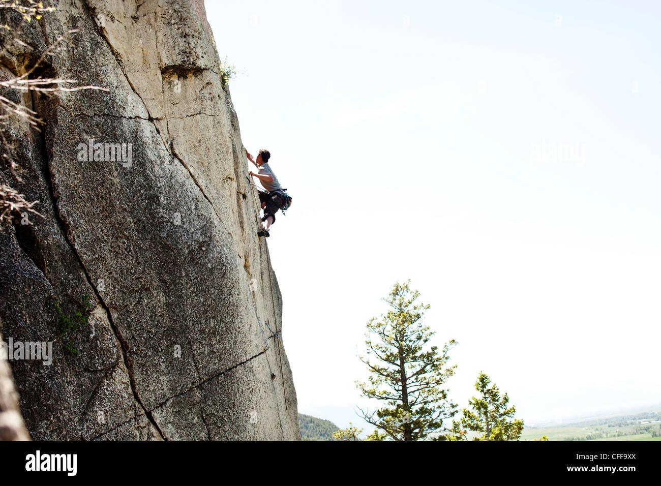 Un hombre atlética escalada alto sobre el suelo en Montana. Imagen De Stock