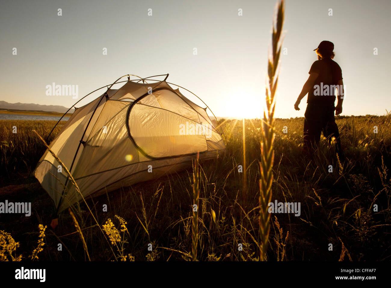 Un hombre de pie junto a su carpa al atardecer en un viaje mochilero en las montañas de Montana. Imagen De Stock