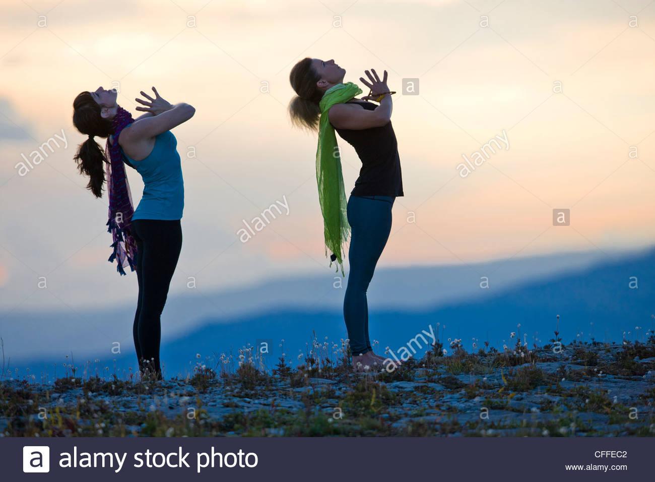 Dos mujeres realizar poses de Hatha Yoga en la cima de una montaña. Imagen De Stock