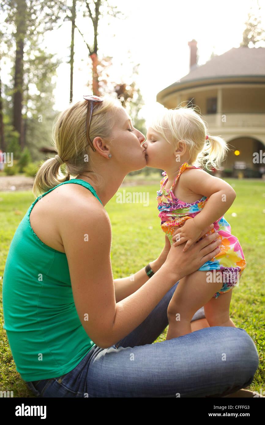Una madre besa a su niña. Imagen De Stock