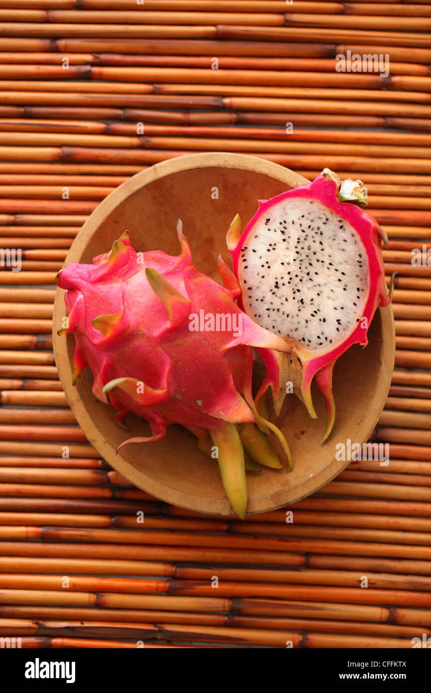 Entero y mitad dragon fruit en recipiente de madera de bambú antecedentes Foto de stock