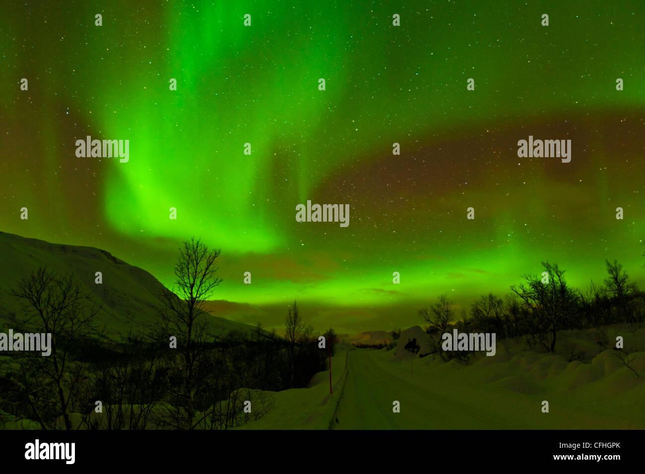 La aurora boreal o luces del norte vistos a lo largo de una carretera cubierta de nieve, Troms, al norte de Noruega, Imagen De Stock