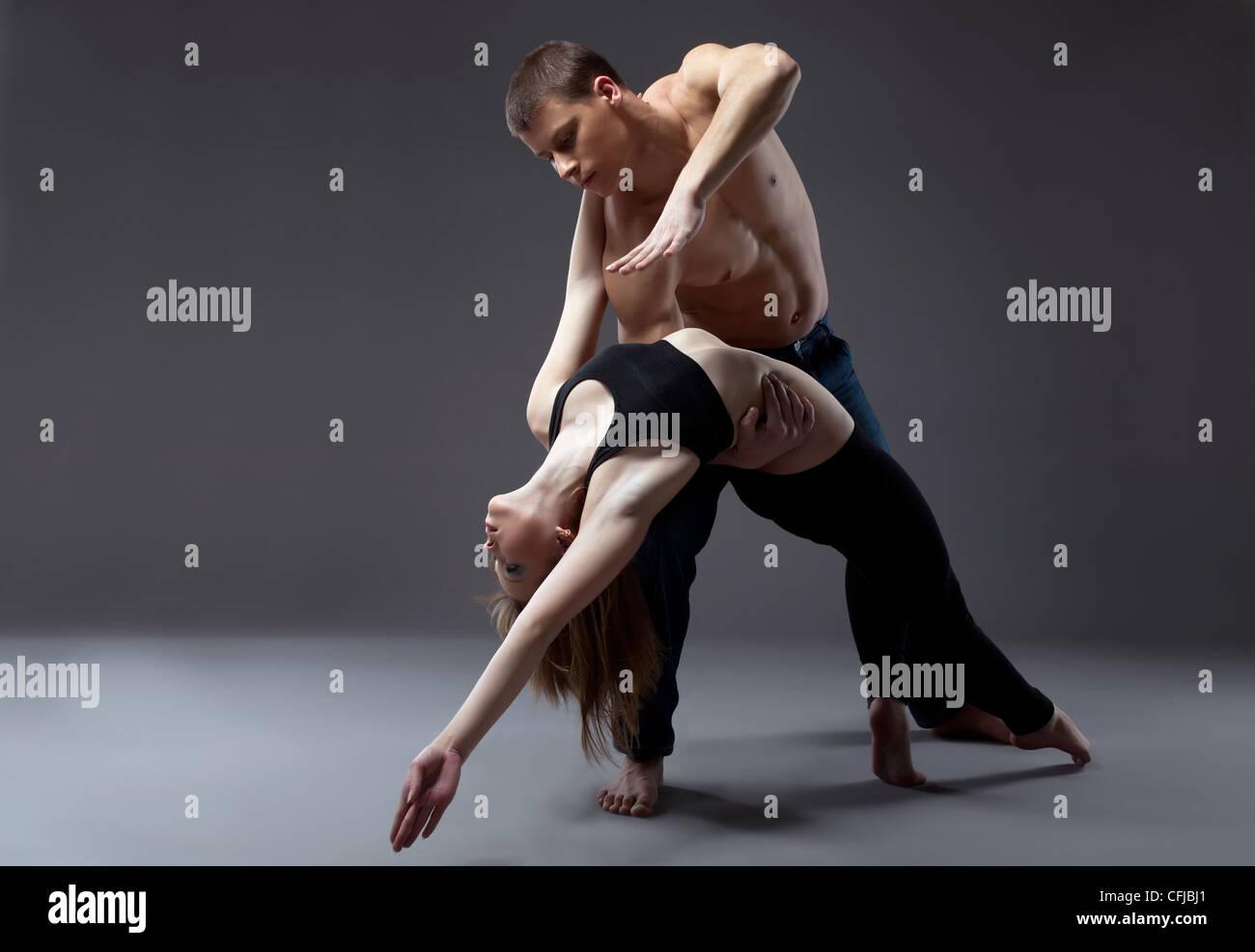 Pareja de jóvenes gimnasta posando en danza aislado Foto de stock