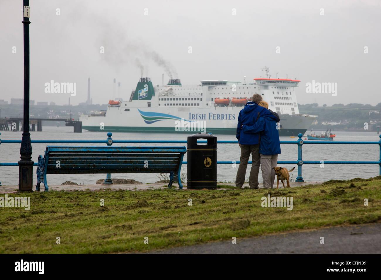 Pareja y su perro mirando el irlandés dejando ferry Pembroke Dock Foto de stock