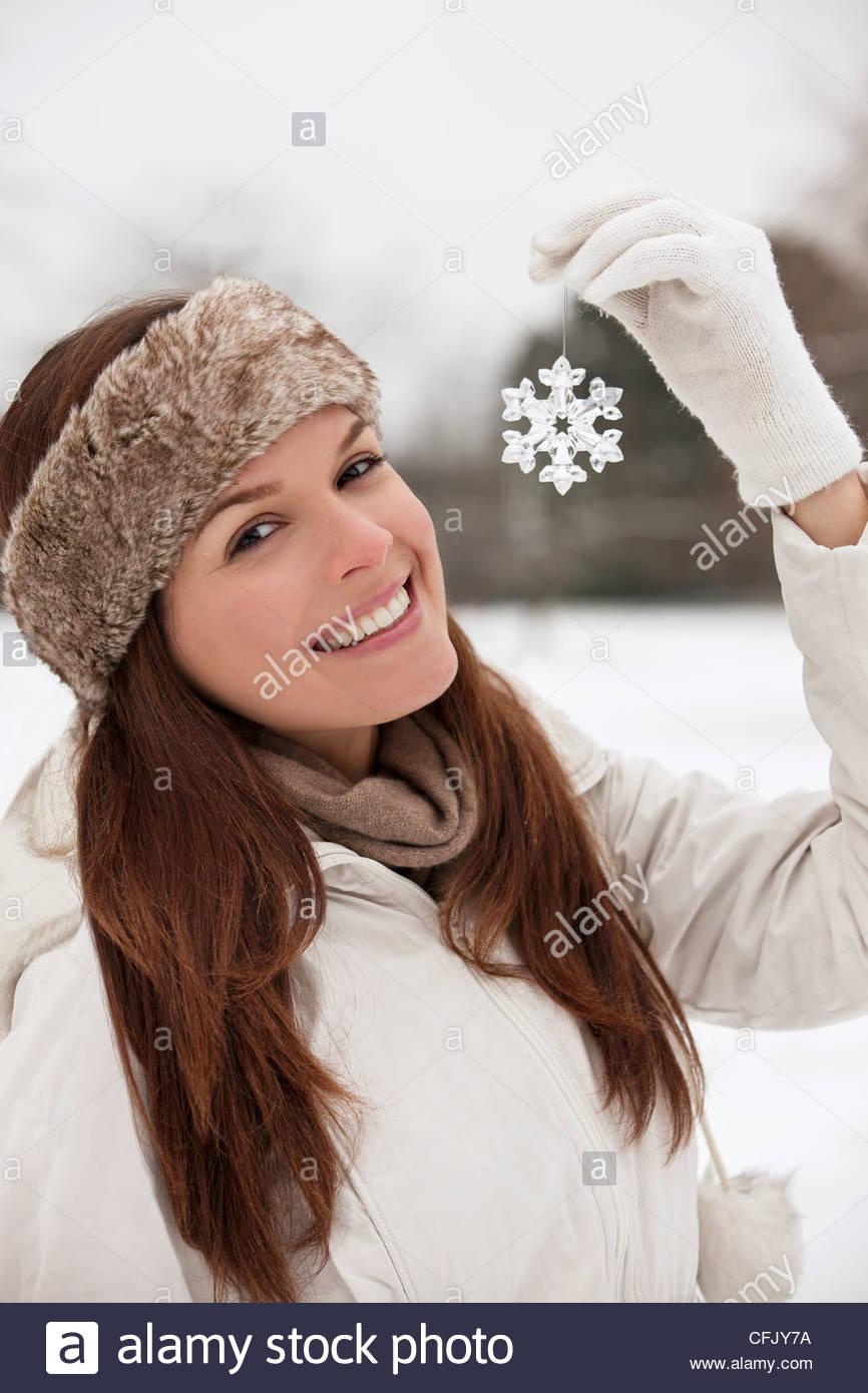 Una joven mujer sosteniendo un copo de nieve decoración Imagen De Stock