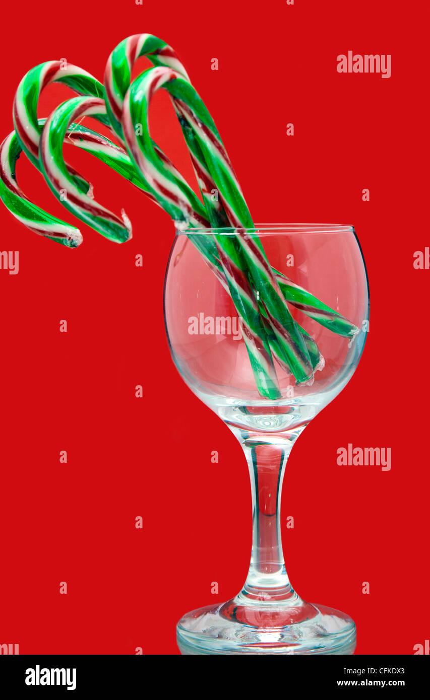 Todavía la vida festiva de la Navidad bastones de caramelo en un vaso de vino sobre un fondo rojo. Imagen De Stock