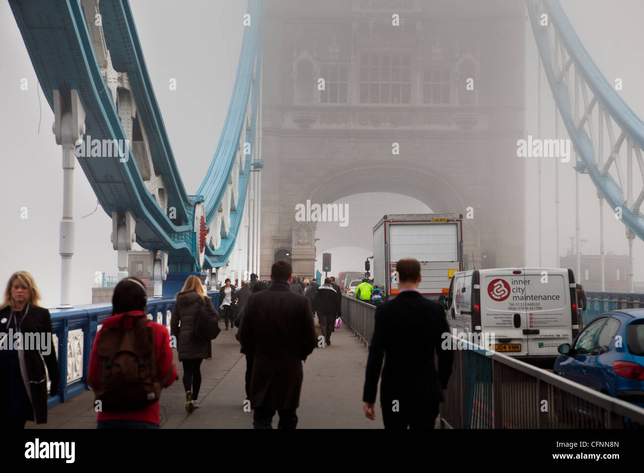 Los viajeros cruzando el puente de la torre a través de la niebla de Londres en el día de la contaminación Imagen De Stock
