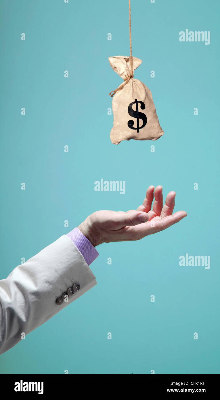 La mano del hombre alcanzar la bolsa de dinero Imagen De Stock