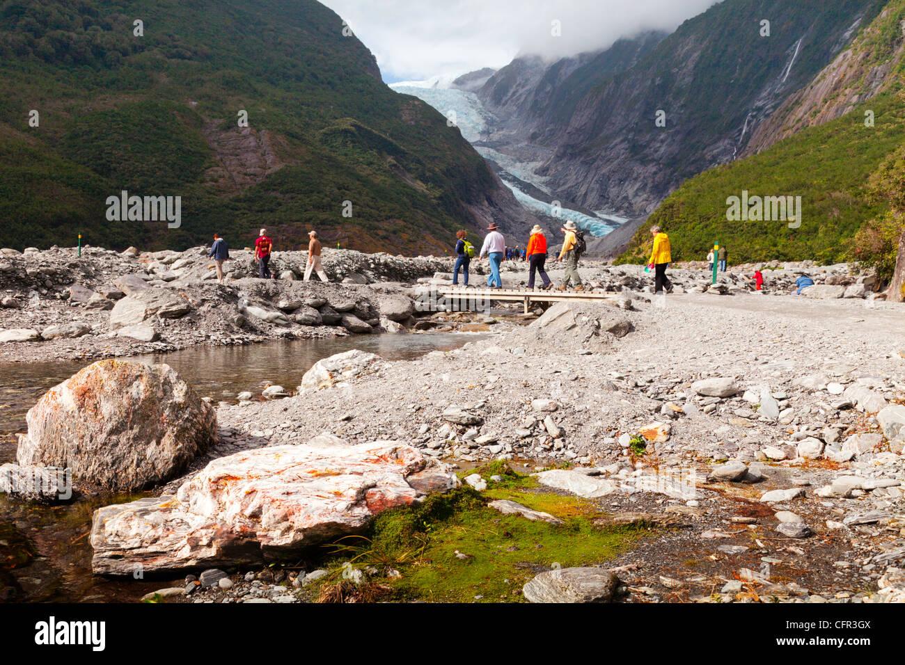 Los turistas que cruzan un puente cerca del glaciar Franz Josef, Costa oeste, Nueva Zelanda. Foto de stock