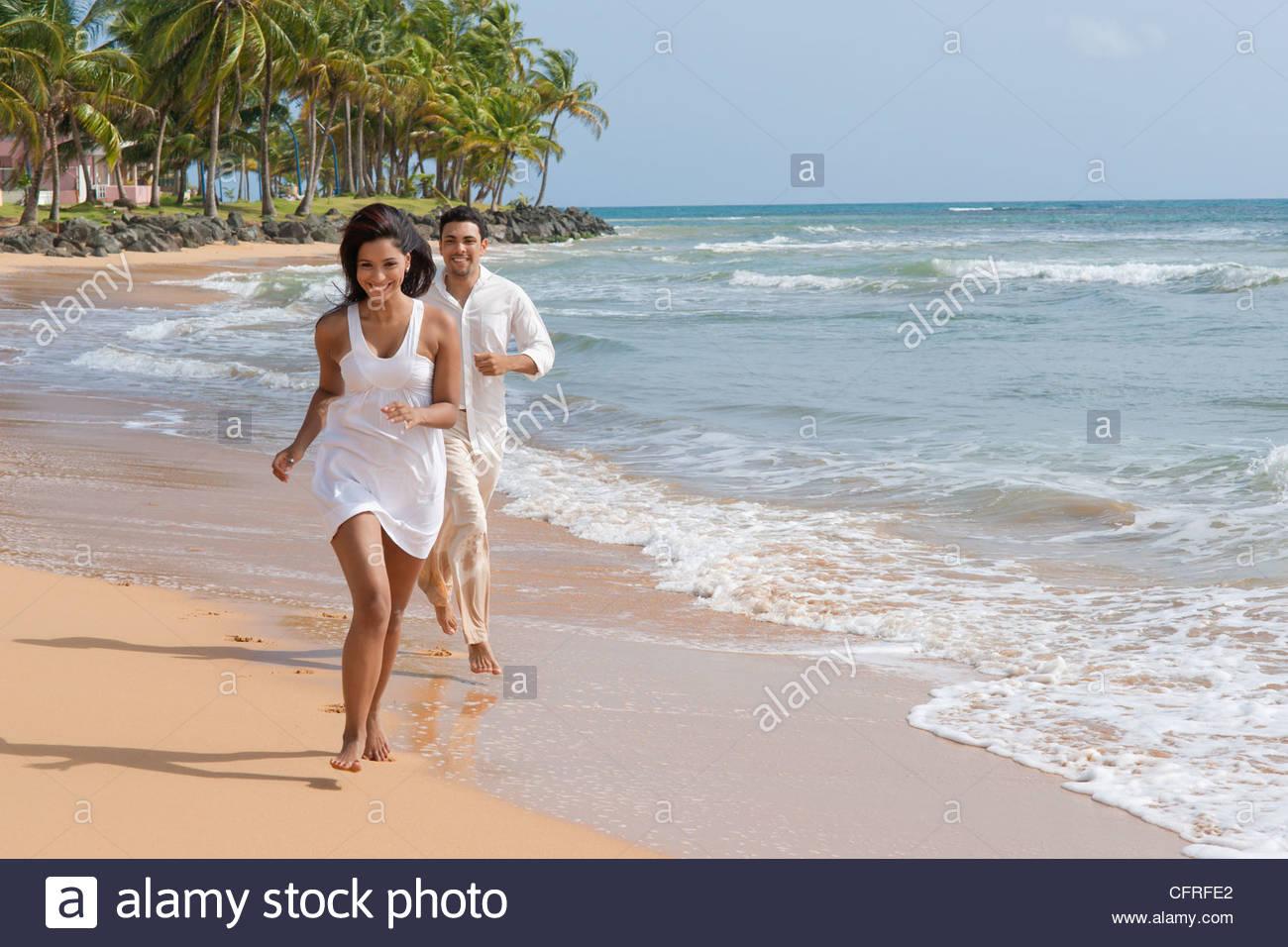 Pareja de hispanos que corre a lo largo de la orilla de la playa de LaPared, Luquillo, Puerto Rico, Estados Unidos Imagen De Stock