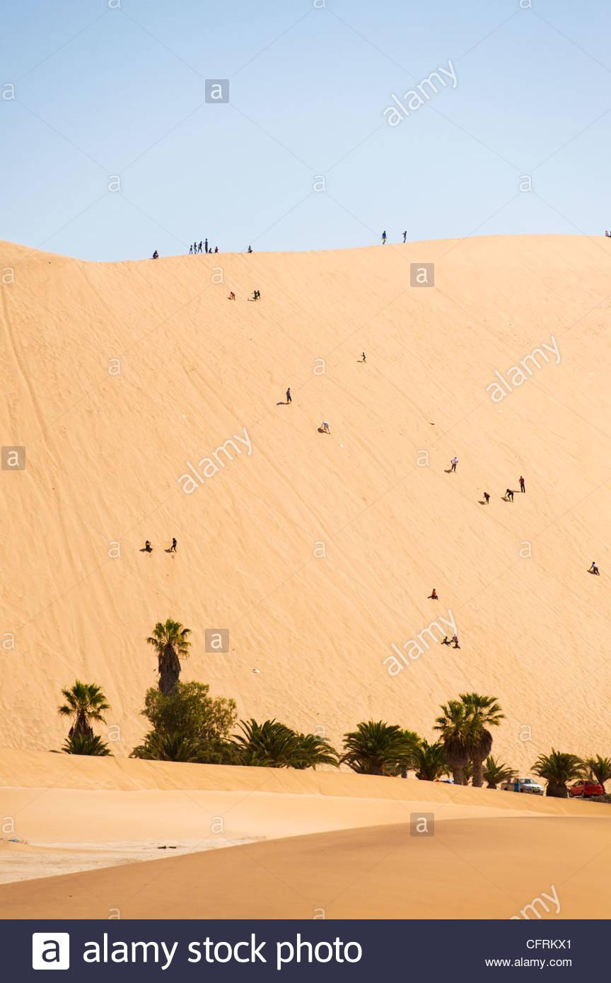 Los turistas escalan Dune 45, cerca de Swakopmund, en Namibia. Imagen De Stock