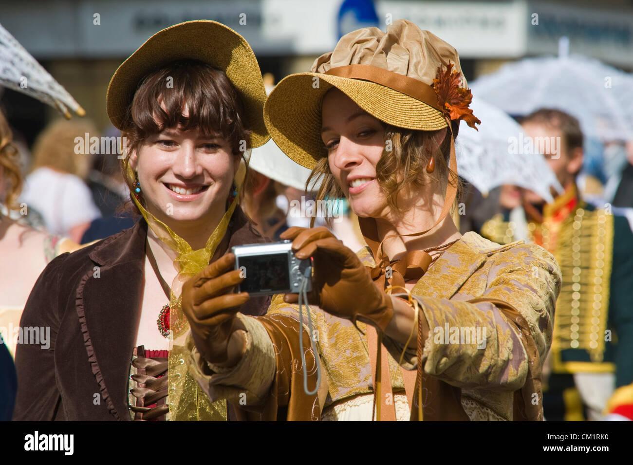 Señoritas en Regency costume fotografiar durante el paseo en el centro de la ciudad de Bath durante 2012 Festival Imagen De Stock
