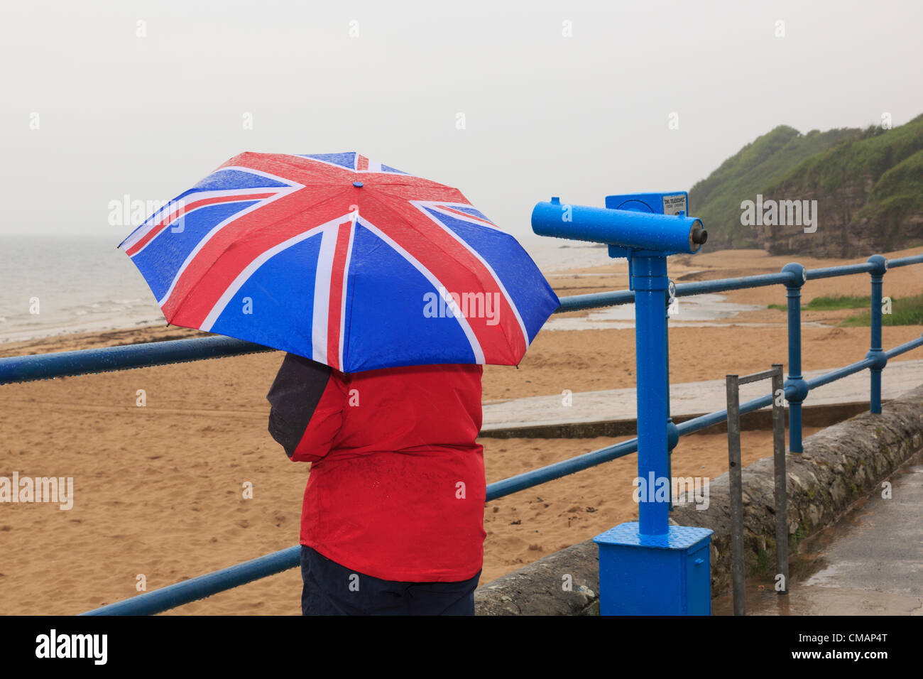 Una mujer mira al mar en el paseo marítimo de la playa desierta con una Union Jack paraguas muy húmeda Imagen De Stock