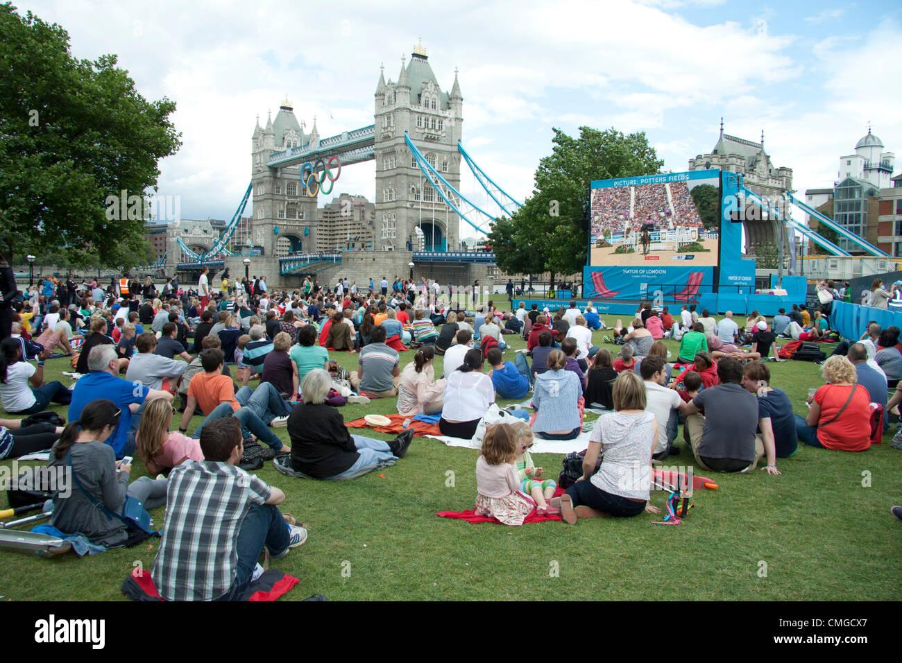 6 de agosto de 2012. Londres, Reino Unido. Una gran multitud de espectadores ver eventos Olímpicos ecuestres en una pantalla grande en campos de alfareros neat Tower Bridge Foto de stock