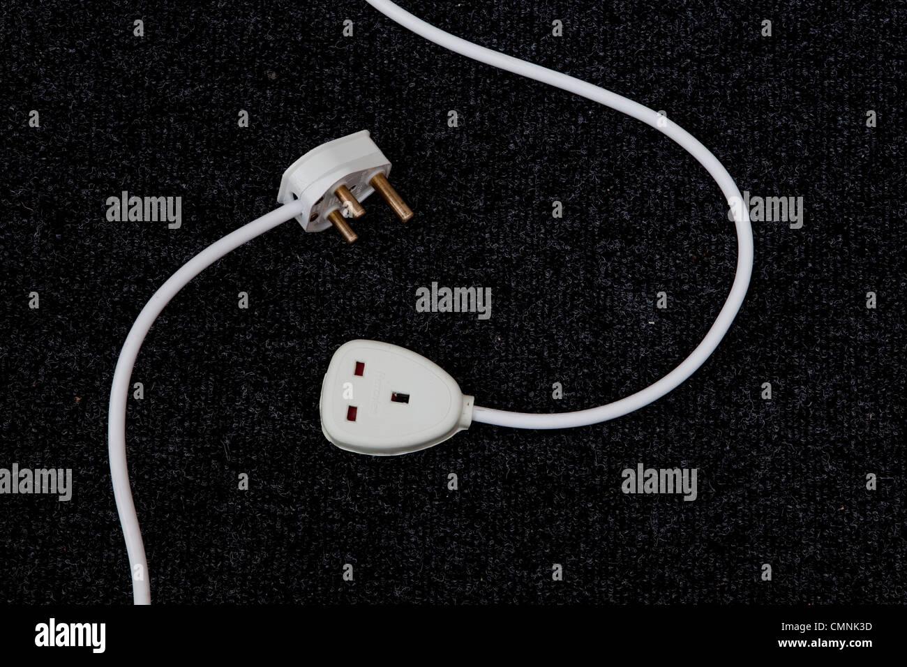 Enchufe y cable de extensión incompatible en alfombras Imagen De Stock