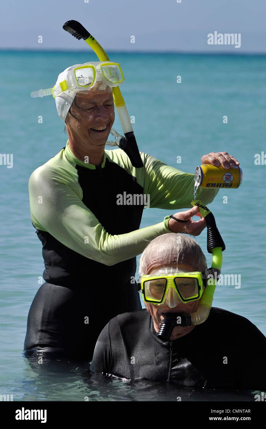 Mujer derramar cerveza abajo su pareja snorkel, Mar de Cortez, en Baja California, México. Foto de stock
