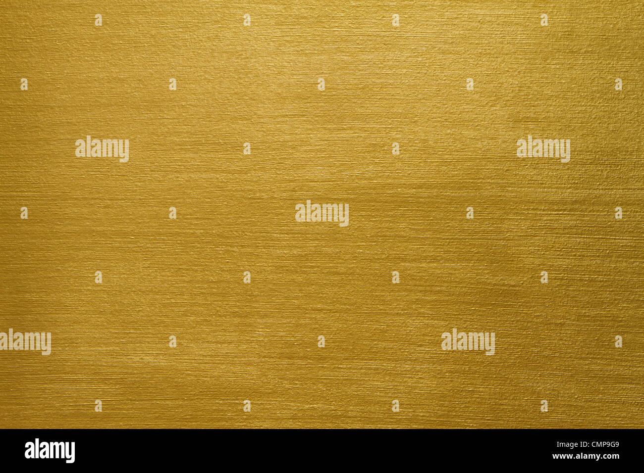 La textura de un muro de cemento cubierto con pintura de oro con pinceladas largas Imagen De Stock