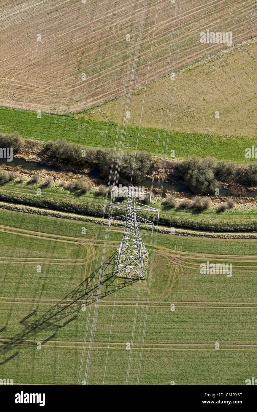 Vista aérea de un poste eléctrico y líneas eléctricas que cruzar un arroyo Imagen De Stock