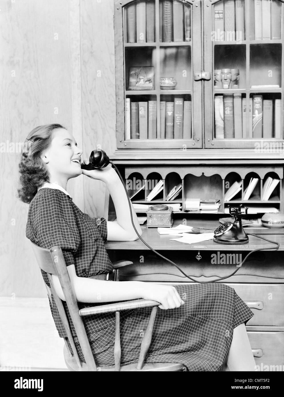 1930 1940 adolescente sentado en una mesa hablando por teléfono dial giratorio negro antiguo Imagen De Stock