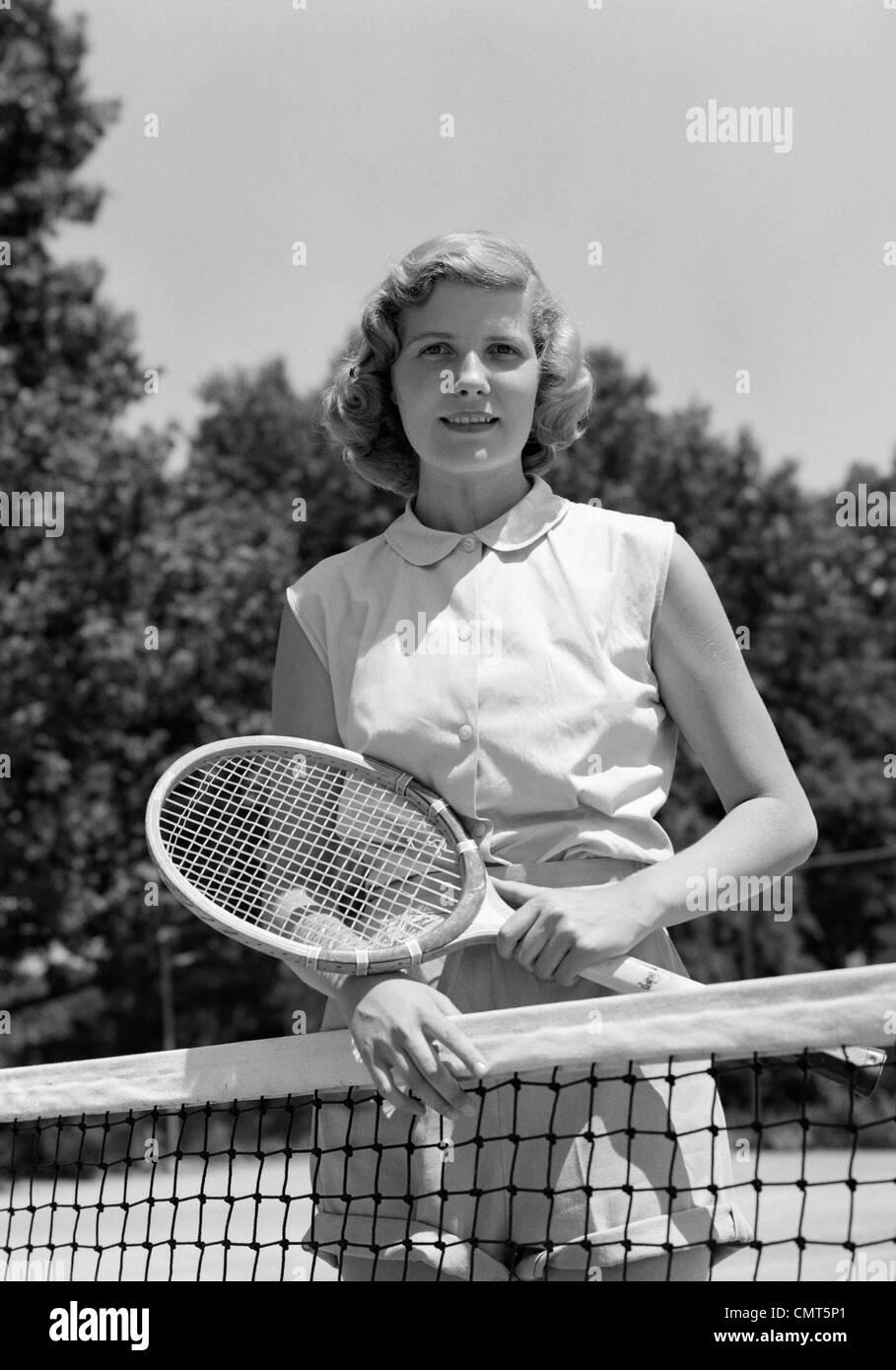 1950 Retrato mujer sosteniendo la raqueta de tenis de pie detrás de NET mirando a la cámara exterior Imagen De Stock