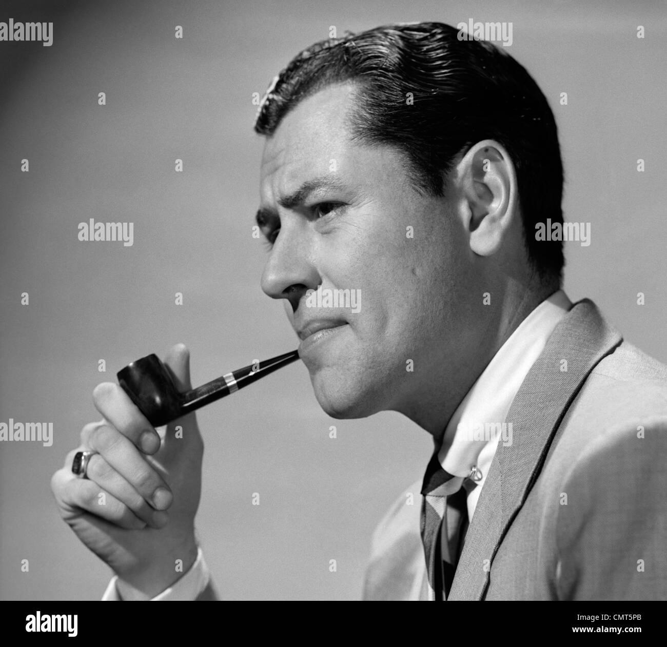 1950 empresario fruncir el ceño en chaqueta y corbata a fumar en pipa Imagen De Stock