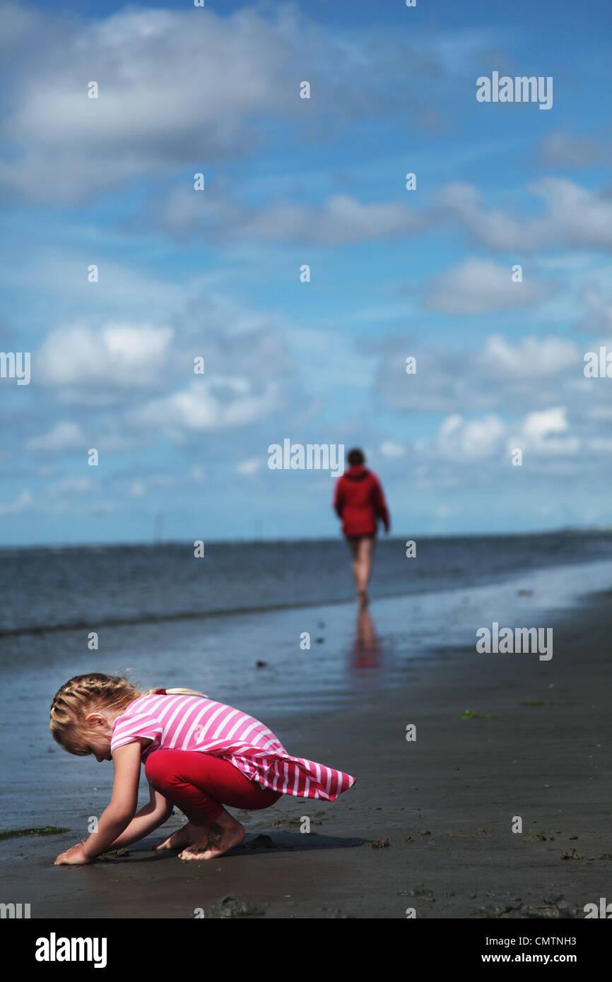 Chica (4-5) jugando con la arena con la madre en el fondo a la playa Imagen De Stock