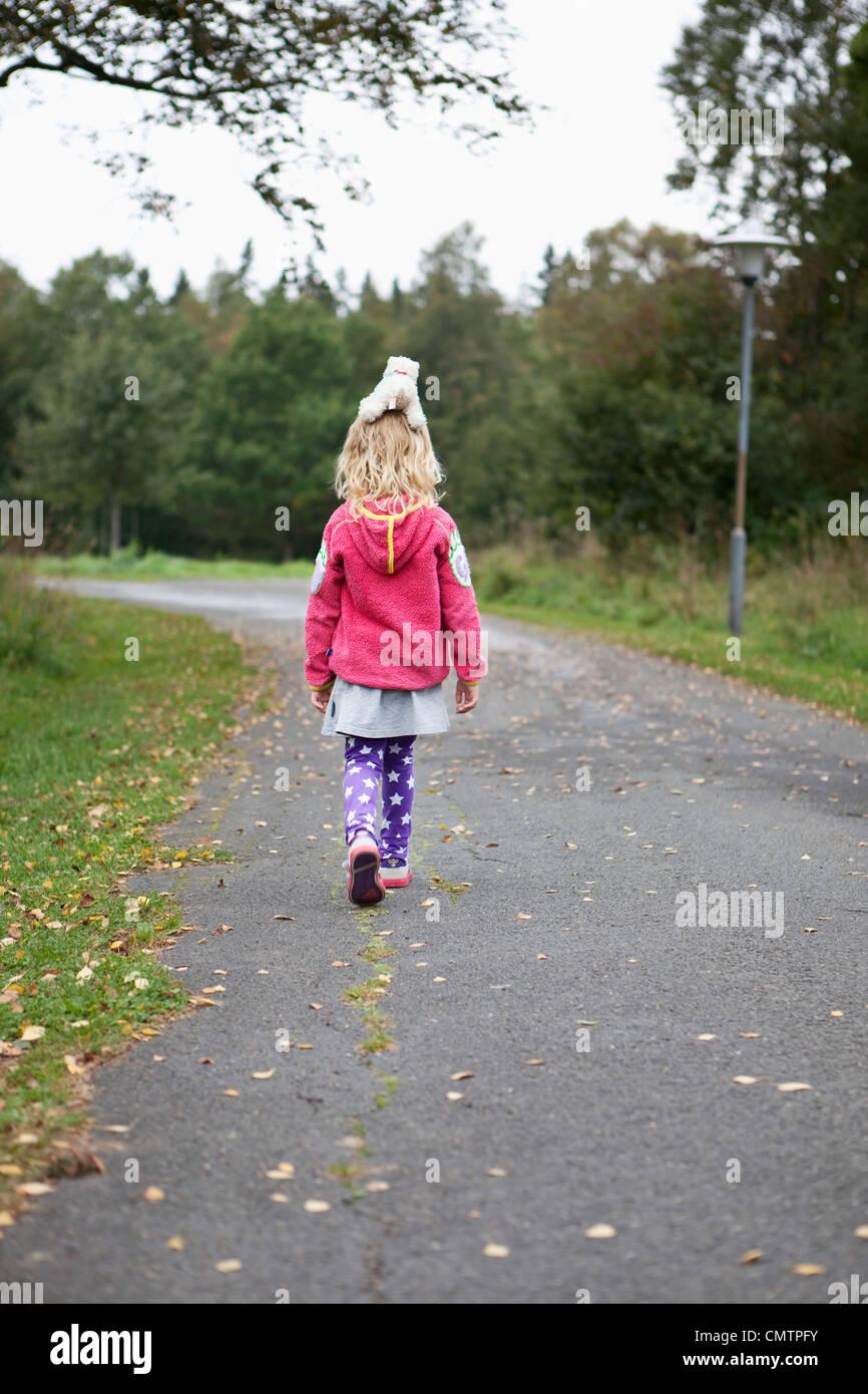 Chica (4-5) caminando en la ruta Foto de stock