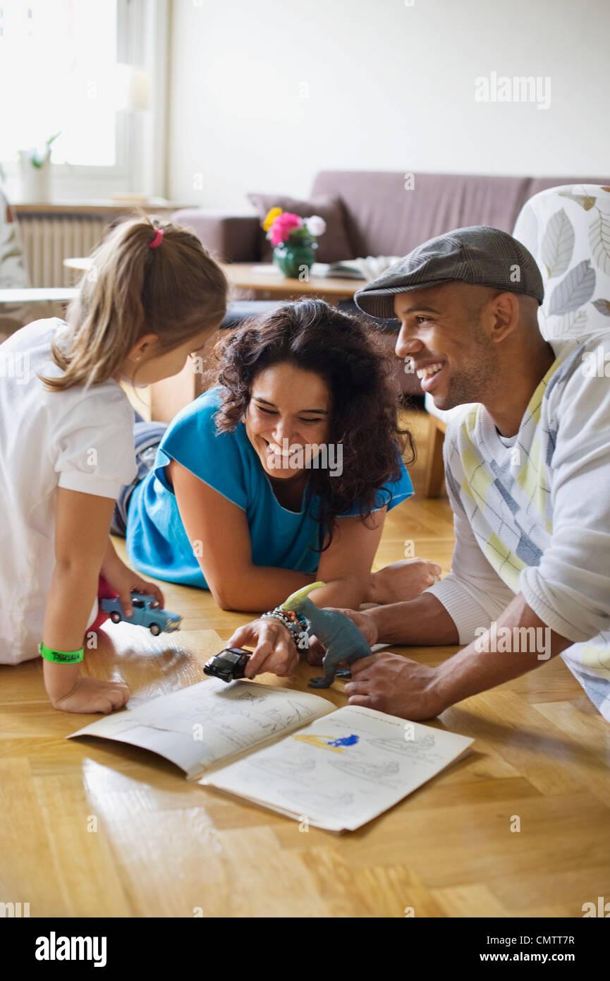 Familia sonriente con su hija (4-5) jugando Imagen De Stock