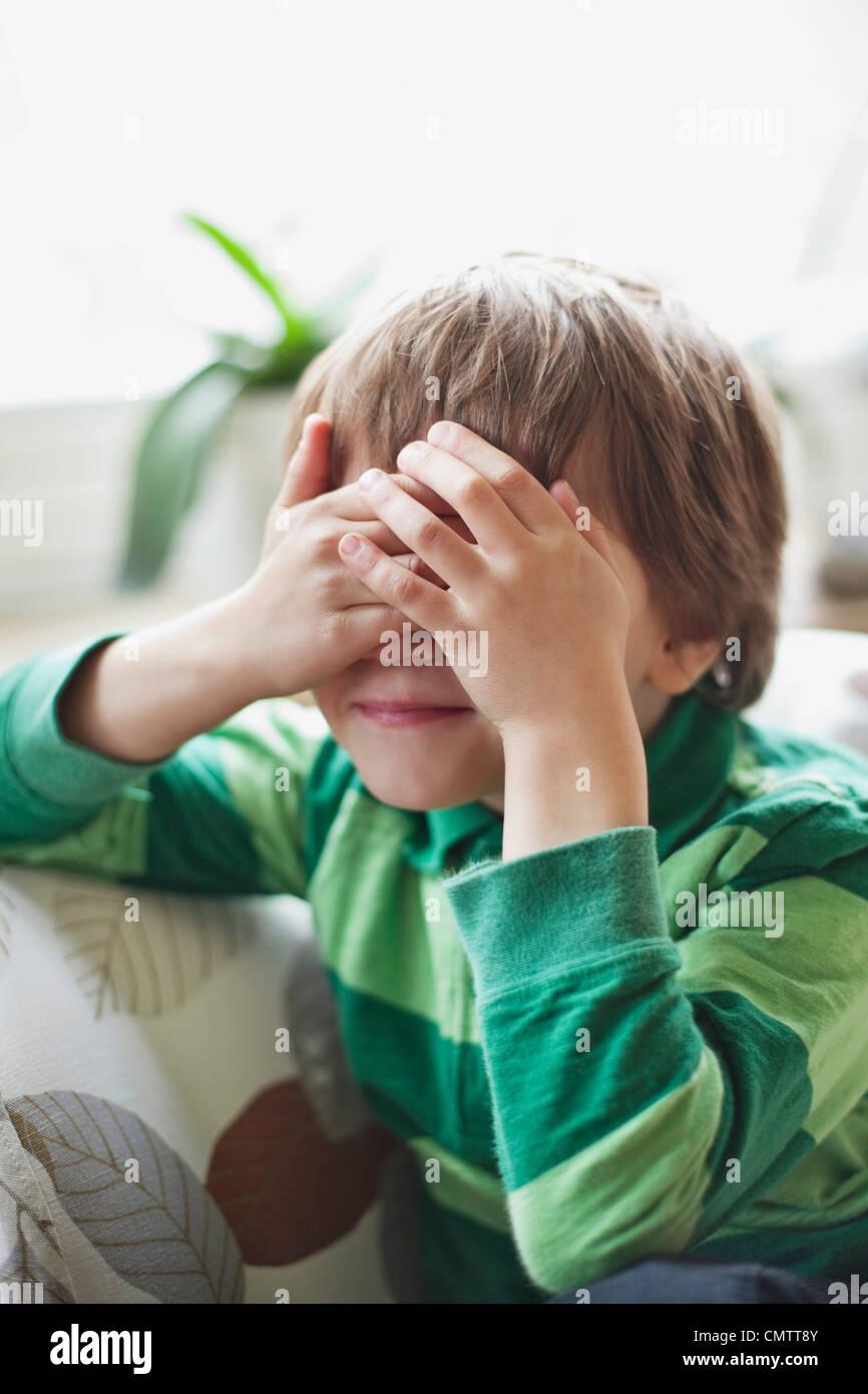 Boy (6-7) que cubre sus ojos Imagen De Stock