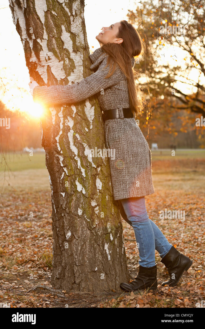 Alemania, Berlín, Wandlitz, mitad mujer adulta abrazando árbol Imagen De Stock