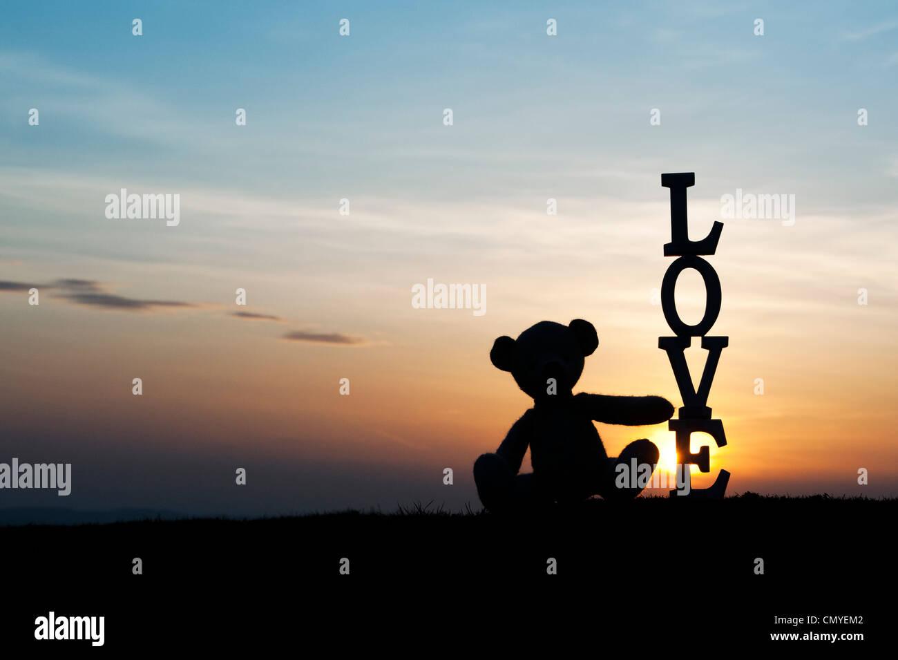 Oso de peluche sentado al lado de la palabra amor al atardecer. Silueta Imagen De Stock