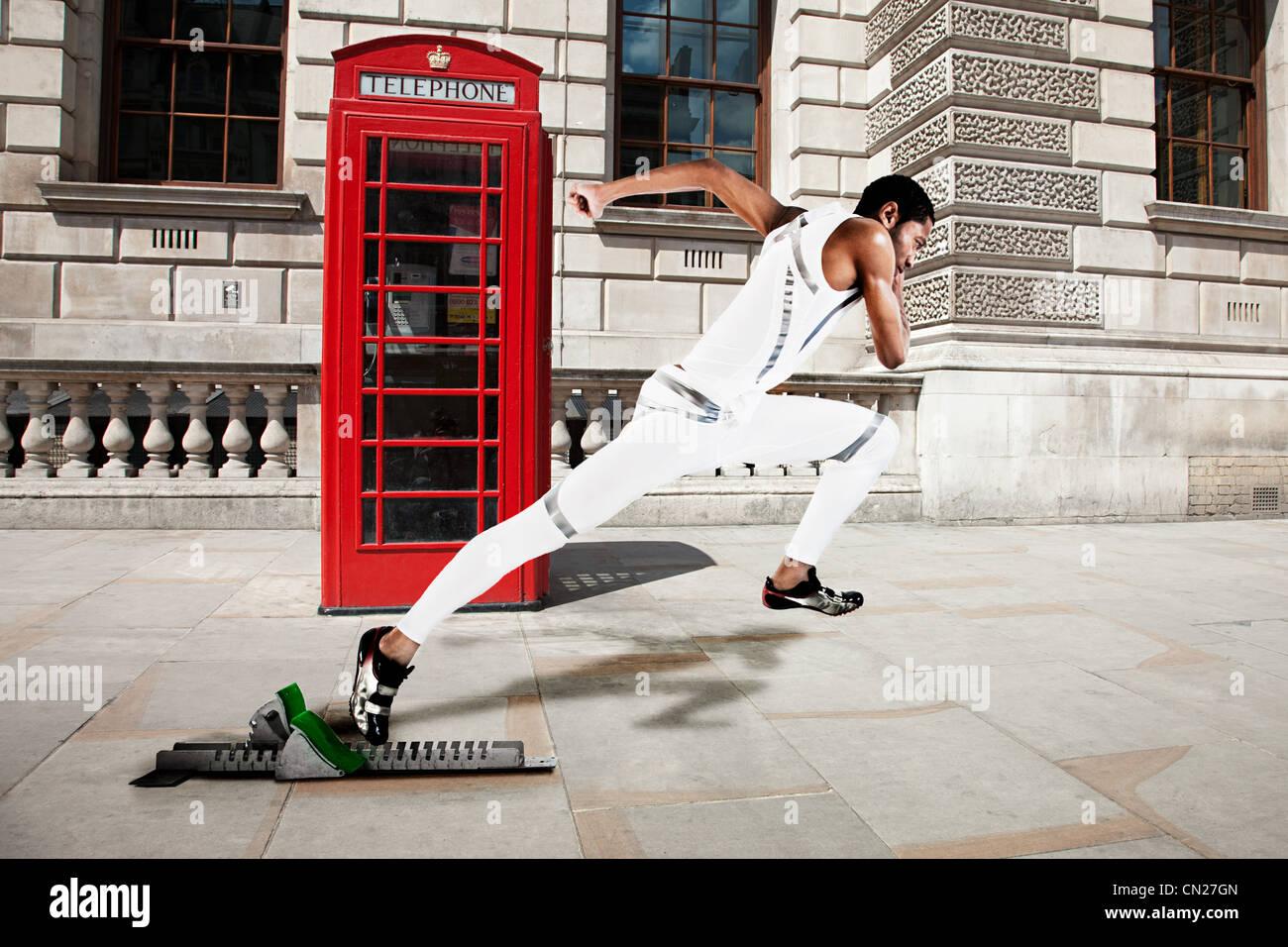 Velocista olímpico en la línea de salida con la caja del teléfono rojo en segundo plano. Imagen De Stock