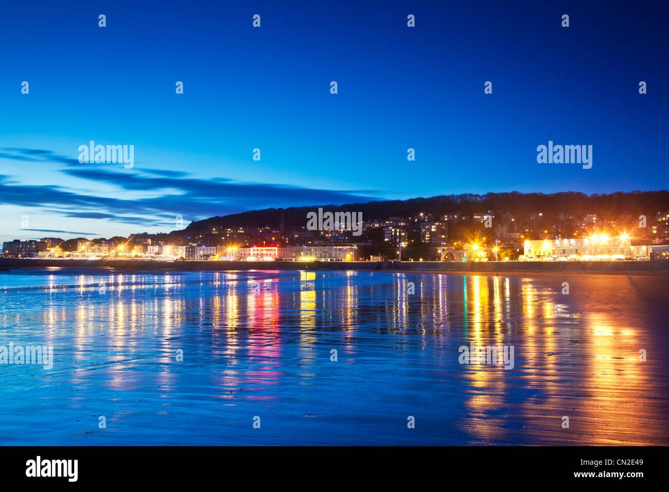 Twilight en Weston-Super-Mare, Somerset, Inglaterra, Reino Unido, con las luces de la ciudad reflejadas en la arena Imagen De Stock