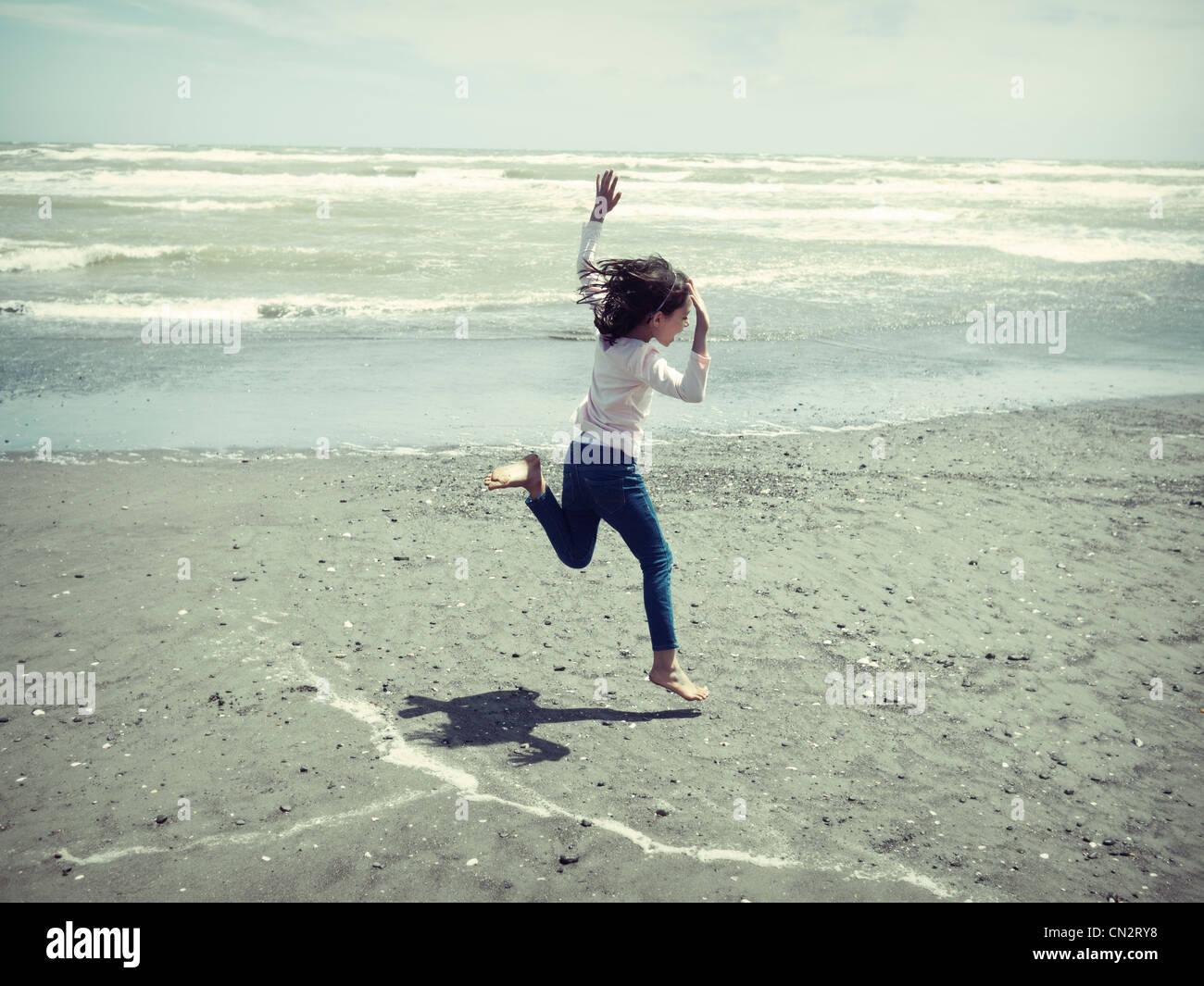 Chica salta en la playa. Imagen De Stock
