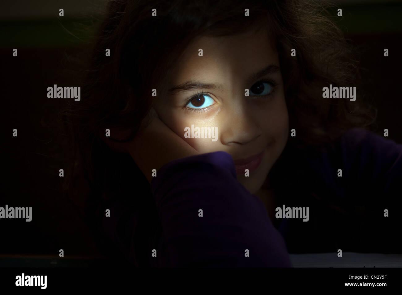 Chica mirando a la cámara desde la oscuridad, cerrar Imagen De Stock