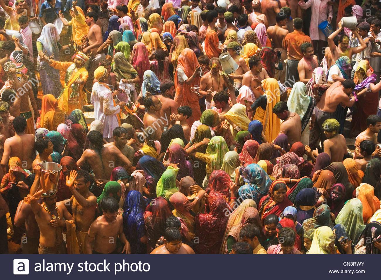 Una colorida muchedumbre de gente celebran el festival de Holi, Mathura, en Uttar Pradesh, India Imagen De Stock