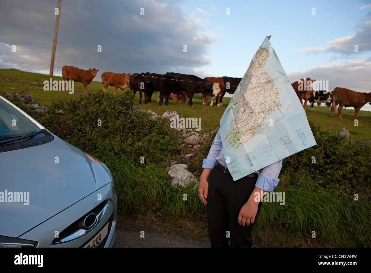 Empresario de pie por Campo y cubierto en un mapa de carreteras Imagen De Stock