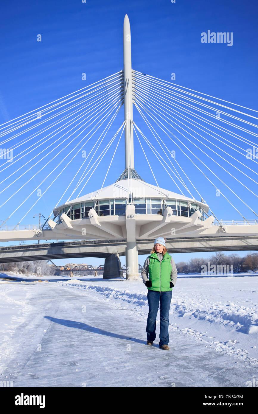 Mujer paseando el congelado Río rojo delante de la Explanada Arador Bridge, las horquillas, Winnipeg, Manitoba Foto de stock