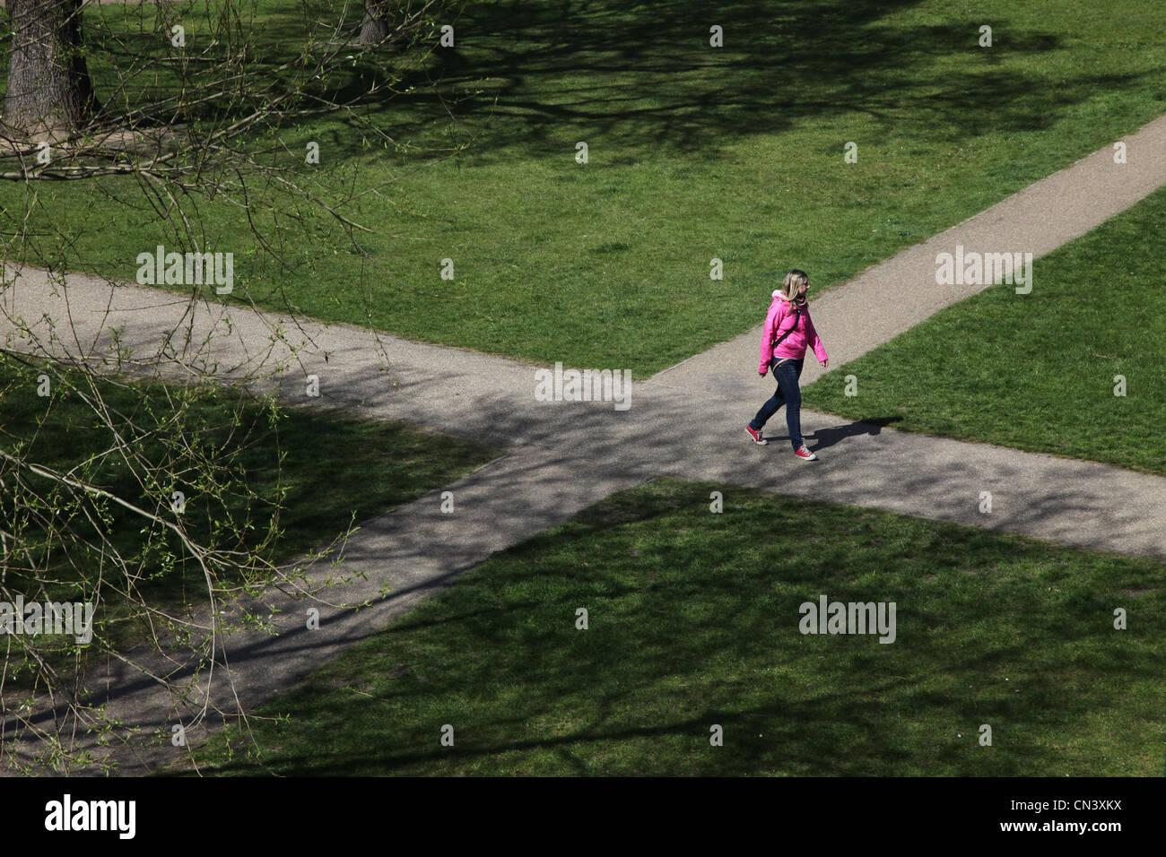 Una mujer en una encrucijada ruta, tomar una decisión sobre qué camino tomar. Imagen De Stock