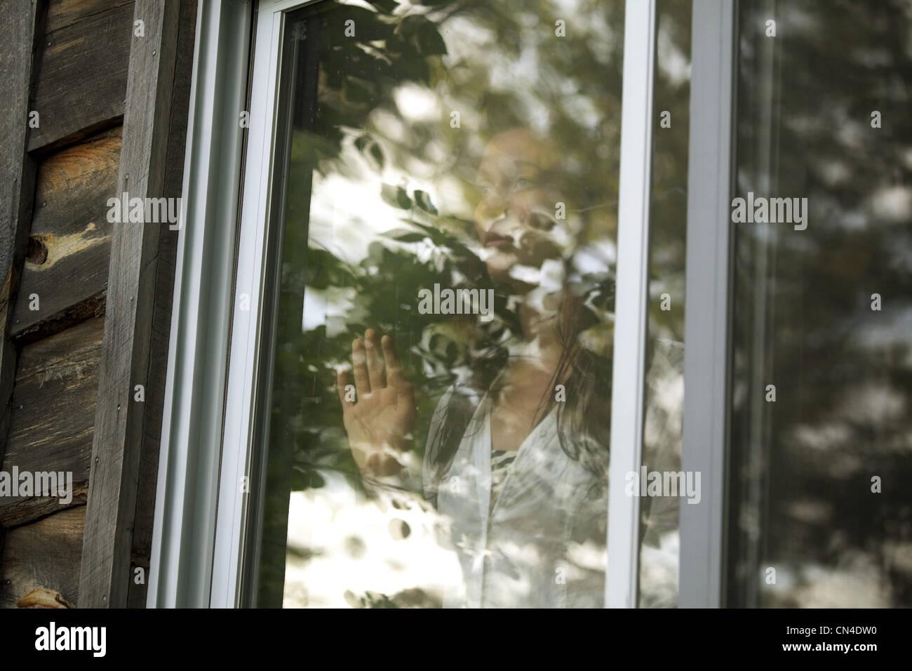 Adolescente mirando a través de la ventana Imagen De Stock
