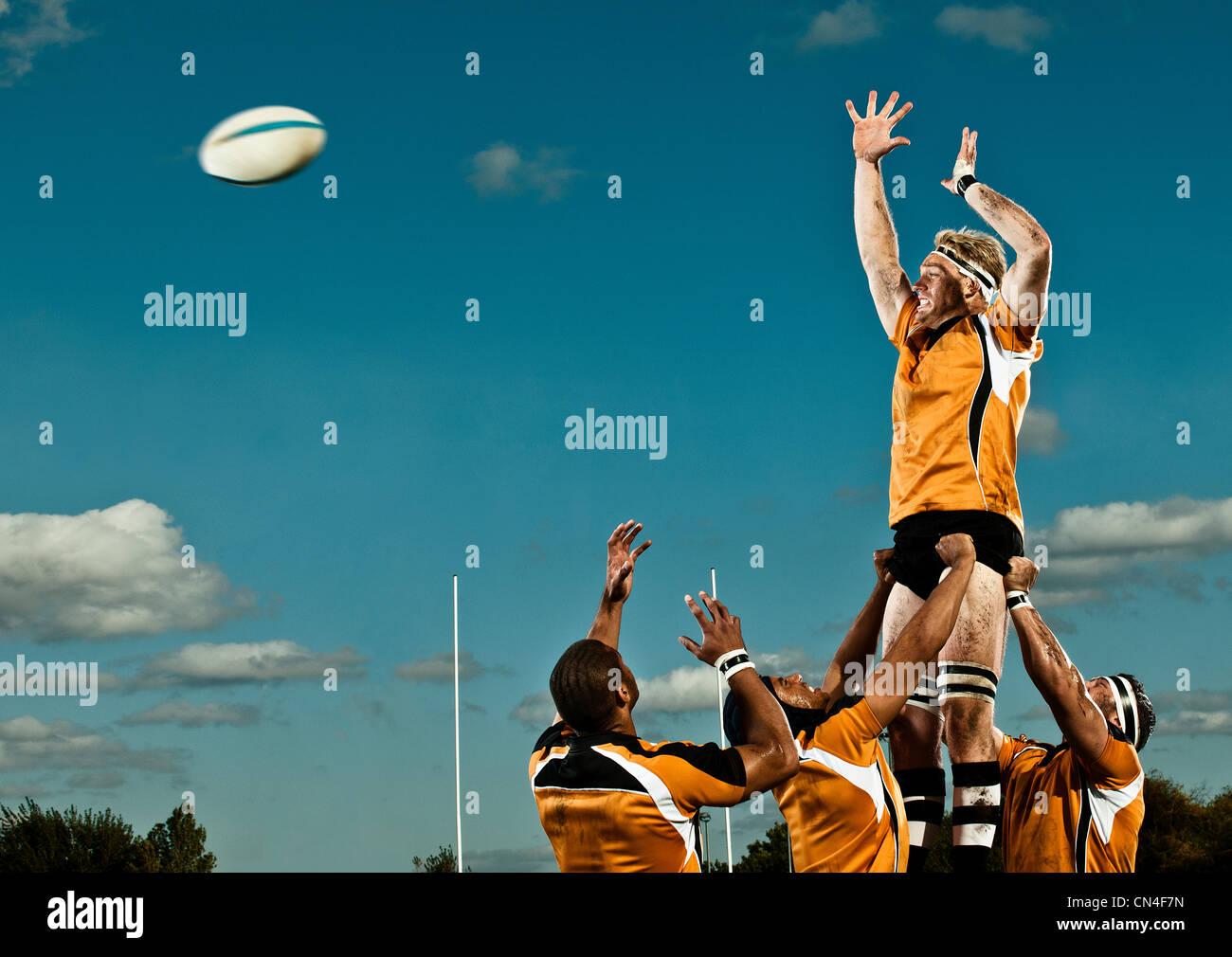 Jugador de rugby saltando para atrapar la bola Imagen De Stock